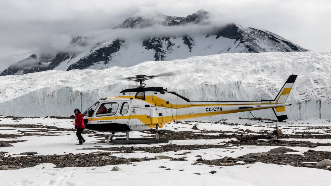 A helicopter sits on land while a guest walks around the snowfield at Taylor Valley, Dry Valleys, McMurdo Sound, during the Spectacular Ross Sea: West Antarctica Cruise.