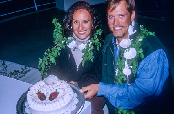 A happy couple smiles and holds their wedding cake off a table, they are celebrating their nuptials on a small ship Alaska cruise.
