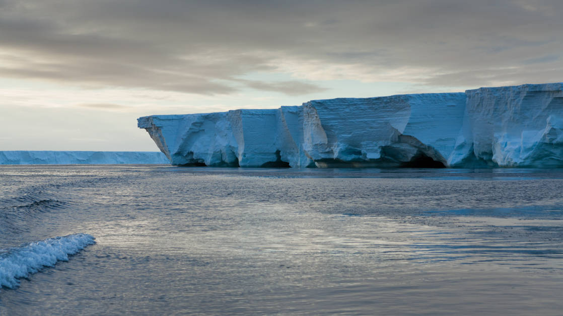 The brilliant blue Ross Ice Shelf with fading warm light, seen during the Spectacular Ross Sea: West Antarctica Cruise.