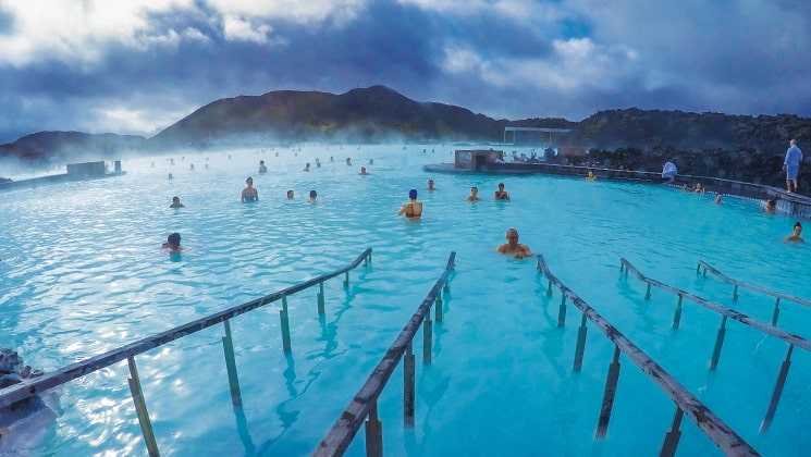 Railings lead into the turquoise blue waters of the Blue Lagoon with steam rising and people bathing, during the Wild Iceland Escape arctic cruise.