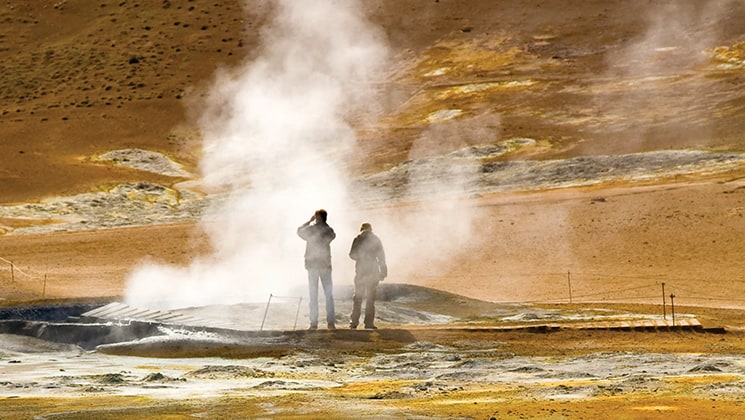 Two travelers stand beside a geyser emitting steam with earthtone rock all around during the Wild Iceland Escape arctic cruise.