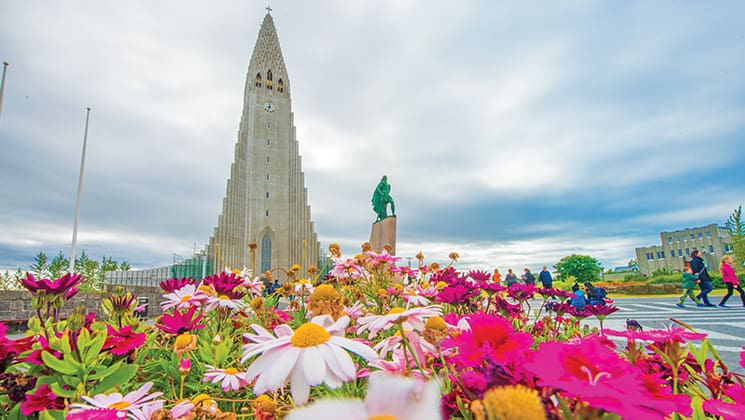Bright fuchsia and white daisies grow in front of the pyramid-shaped Hallgrimskirkja Church in Reykjavik with a green person statue in front, seen the Wild Iceland Escape arctic cruise.
