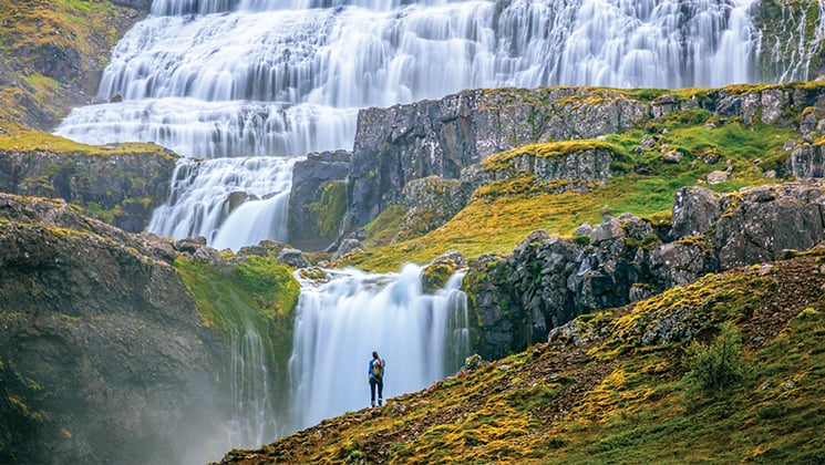 Waterfalls cascade over verdant green rolling hills as a traveler stands in front, during the Wild Iceland Escape arctic cruise.