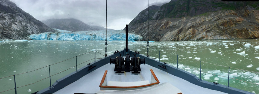 a panoramic photo from the bow of the small Alaskan ship the Westward. Beyond the bow is a teal icy glacier at the end of a fjord seen on an Alaska small ship cruise.