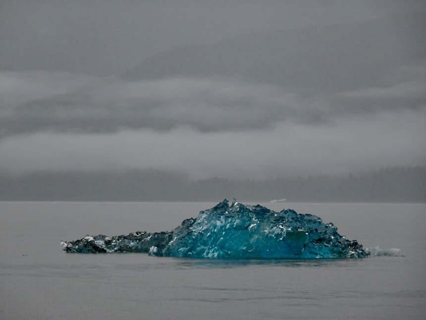 an all grey sky and water are only brought color by a large teal blue iceberg that floats in the water of Alaska's Inside Passage. Seen from the Westward small ship.