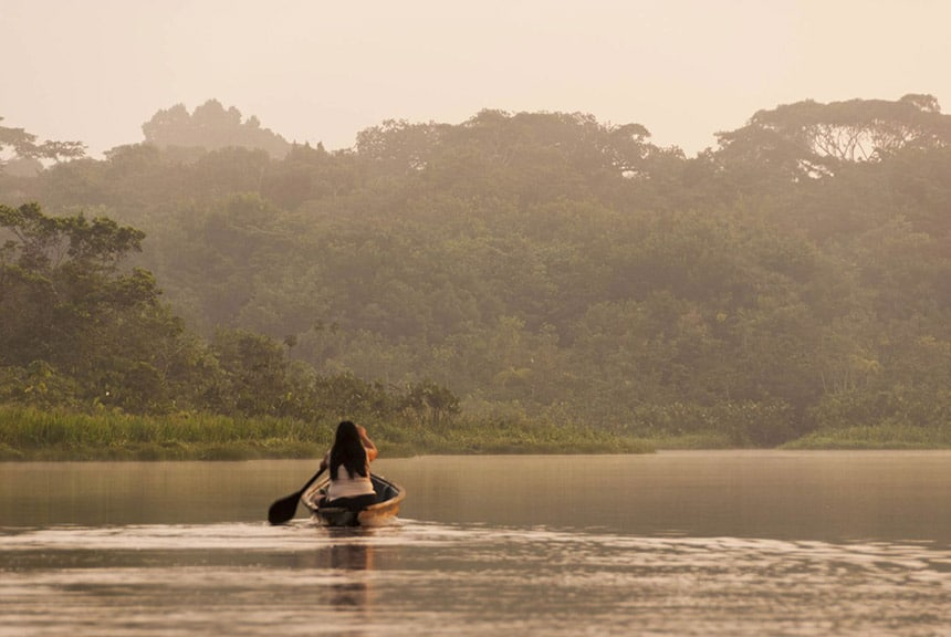 The sun is setting in Ecuador. On Anangu Lake, a woman paddles a wooden canoe away from the camera, it is hazy with a light sepia tone.