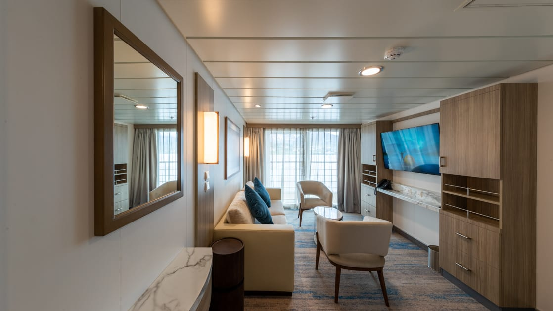 Lounge area of Captain's Suite aboard Greg Mortimer polar ship, with framed mirror on the all, wardrobe, beige couch & 2 chairs, flatscreen TV & sliding glass doors out onto private balcony.