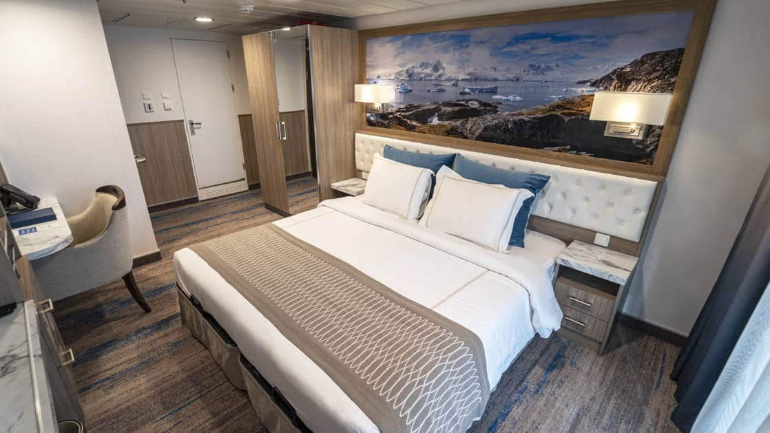 Category B Balcony Stateroom aboard Greg Mortimer polar ship, with white-duvet-covered king bed, marble bedside tables, desk & sliding glass doors onto private balcony.