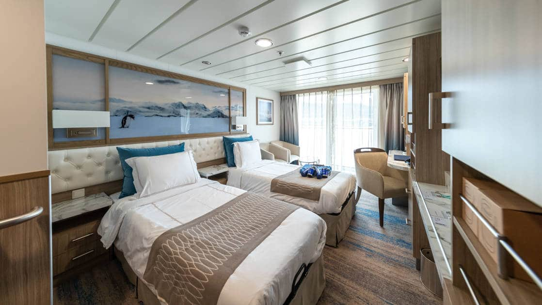 Category C Balcony Stateroom aboard Greg Mortimer polar ship, with 2 white-duvet-covered twin beds, marble bedside tables, tan chair, desk, wardrobe & sliding glass doors onto private balcony.
