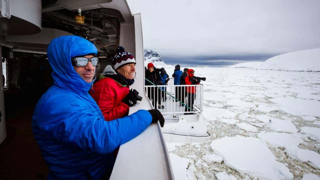 Polar travelers stand out on deck, including a hydraulic viewing platform, as their ship Greg Mortimer breaks through tight sea ice.