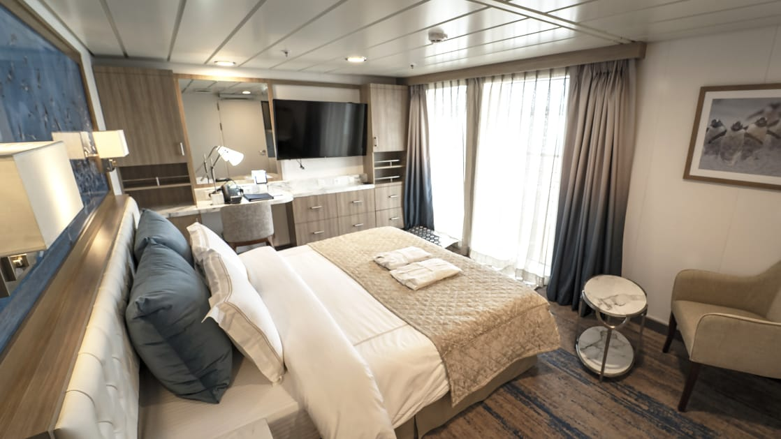 Superior Balcony Stateroom aboard Greg Mortimer polar ship, with beige quilted king bed, marble side table, tan chair, flatscreen TV & sliding glass doors onto private balcony.