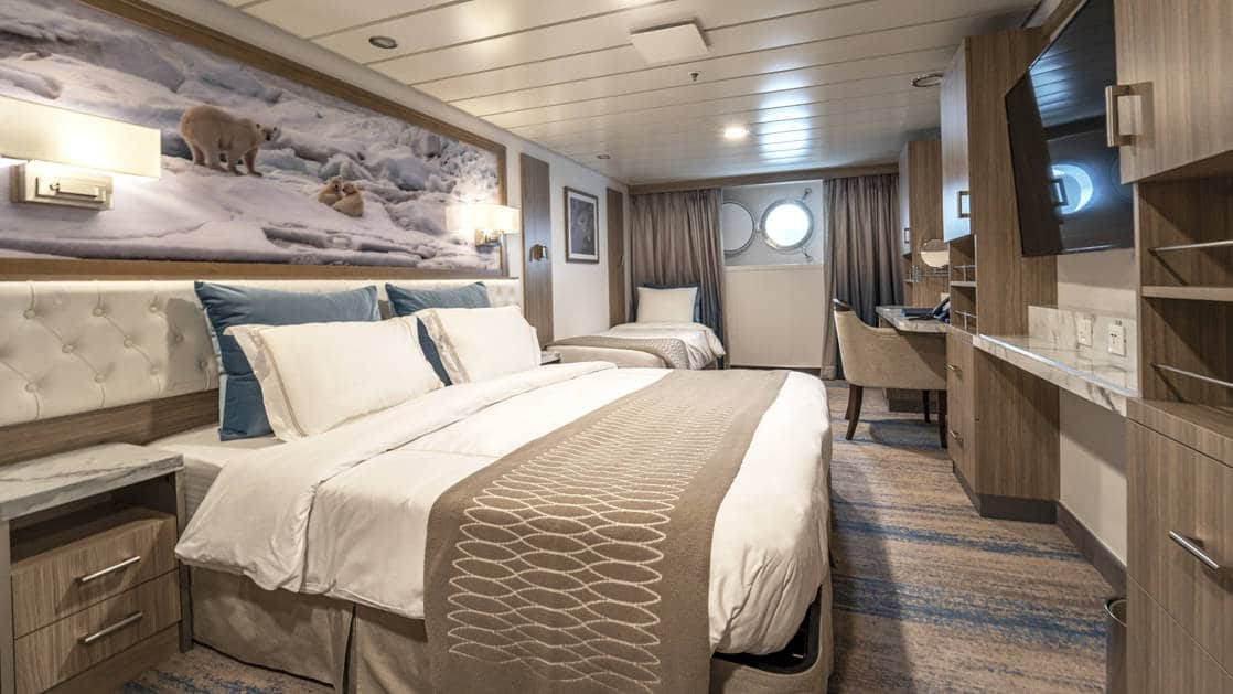 Triple Stateroom aboard Greg Mortimer polar ship, with white-duvet-covered king bed & twin bed, marble bedside tables, tan chair, desk, flatscreen TV, wardrobe & porthole.