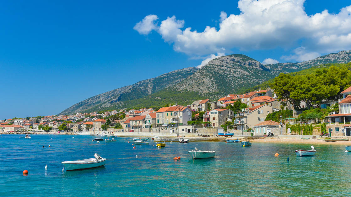 Seaside town of Brac with small fishing boats, white-sand beach & terra cotta-roofed homes, seen during the Best of Croatia luxury cruise.