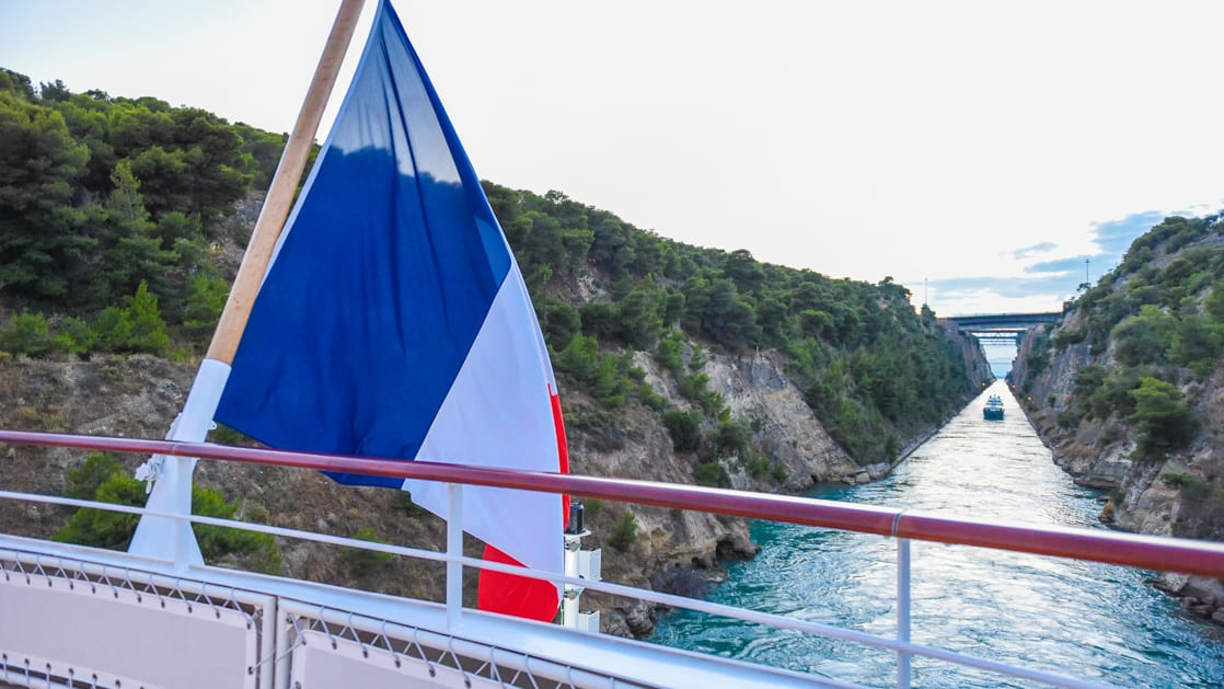 A French flag flies from the aft upper deck of a luxury small ship as it cruises through the narrow Corinth Canal, lined by greenery and tall rock walls, during the Best of Croatia Cruise.