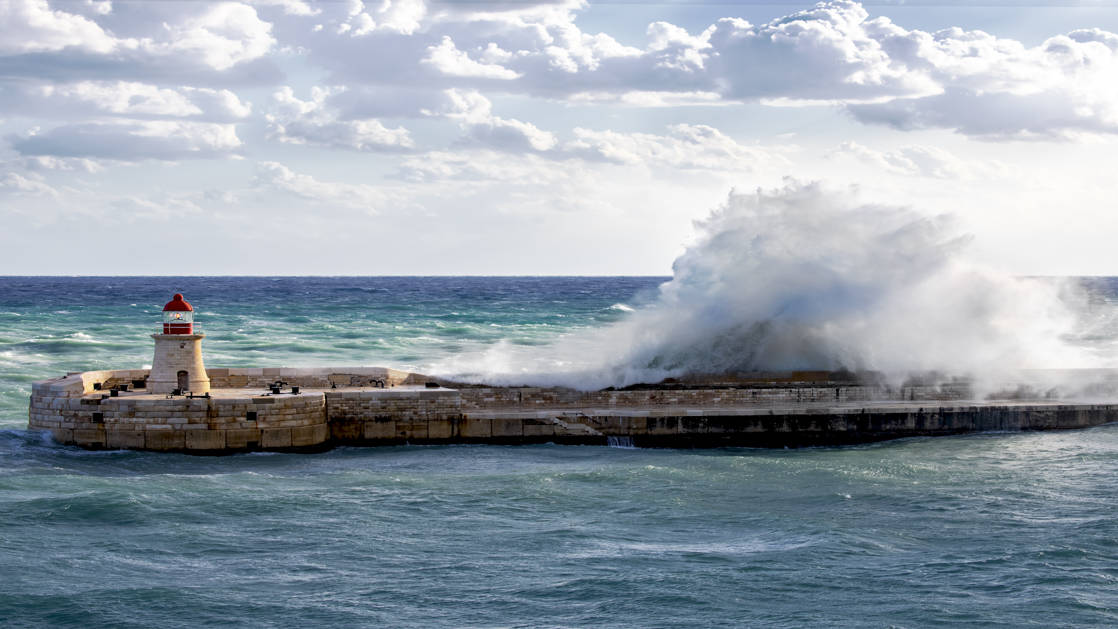 A large wave slams into a sea wall on a partly sunny day in the Mediterranean during the Best of Croatia Cruise.