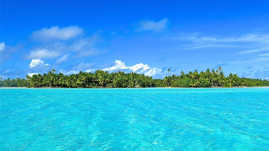 crystal clear teal water split from the blue sku with a lush palm tree filled island in French polynesia.