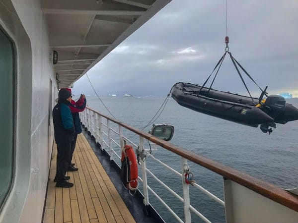from deck four of hebridean sky polar expedition ship, the ships railing surrounds a path, outside of it a black zodiac raft is being lifted and let down into the water