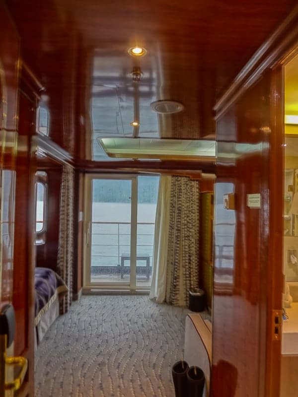 a rich wooden suite cabin aboard hebridean sky polar expedition ship shows the end of the bed and a sliding glass door out to a private balcony.