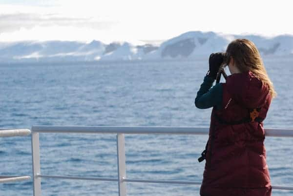 from the deck of hebridean sky polar expedition ship , a female guest faces out toward the sea with binoculars to her eyes looking for birds
