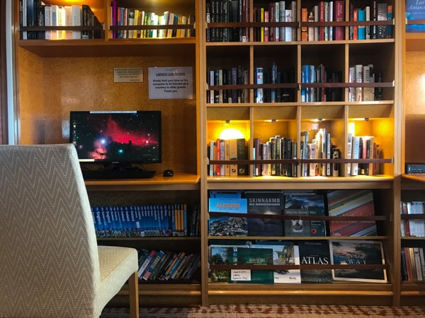 The library aboard hebridean sky polar expedition vessel a chair with a wall full of cubbies and books, and a computer sits on a desk.