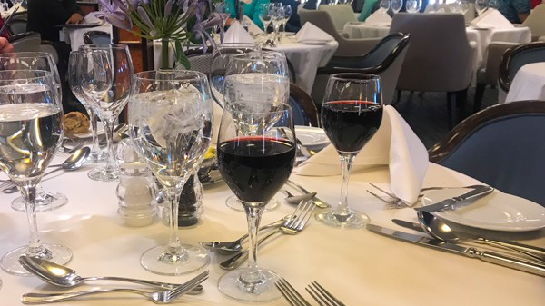 a table with white table cloth and red wine glasses at the restaurant aboard hebridean sky polar expedition ship