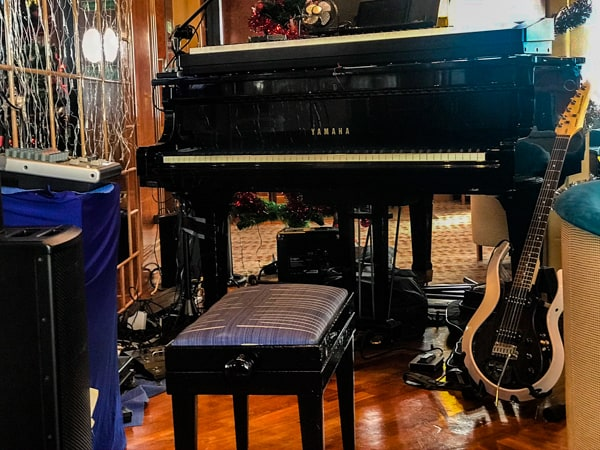 The club aboard hebridean sky polar expedition ship, a black piano is shown available for like music and entertainment
