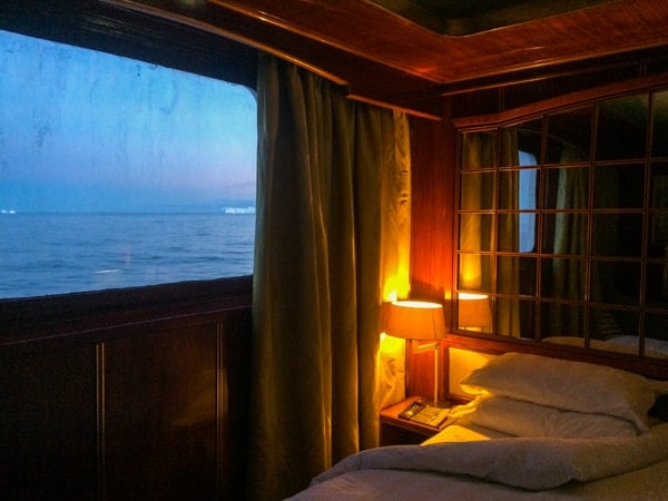 The sun goes down through the window of a suite cabin aboard hebridean sky polar expedition vessel