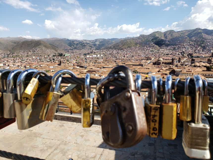 A row of locks hang from a wire bridge in front of of a landscape view of Cusco, seen before departing on a Machu Picchu land tour.
