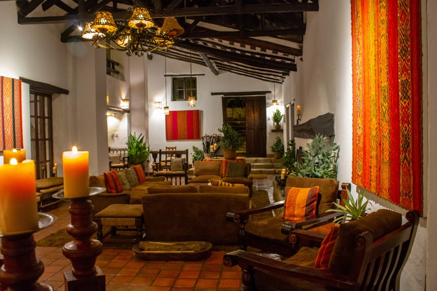 The inside of Inkaterra Machu Picchu hotel during a Peru land tour. Warm orange red and yellow wall hanging decor and candles fill the room with comfy arm chairs and love seats