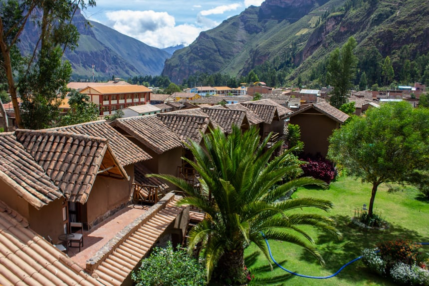 The grounds of Lamay Lodge inside Sacred Valley, Peru. Adoble shingles on top of many roofs are pictured as the lodge sits infront of a lush green mountain range.