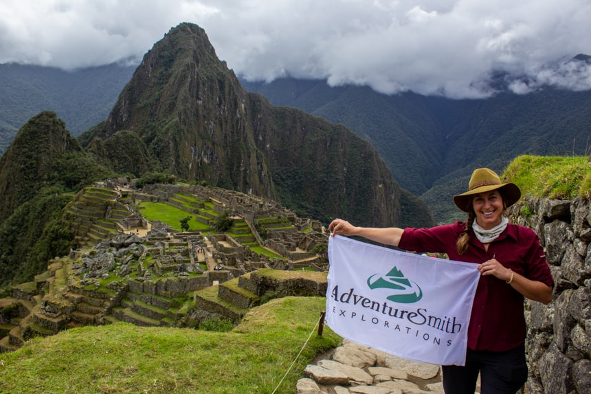 A female traveler stands in front of Machu Picchu, towering green cliff sides with ancient walled town below her as she holds a white AdventureSmith Explorations flag.