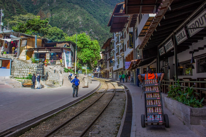 Downtown in Aguas Calientes, Peru. A view from the train tracks that split the city buildings. People are walking around the streets infront of large green mountainside