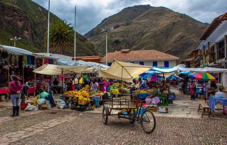 An outdoor market in the Sacred Valley of Peru. Umbrellas stand over tables filled with fruits, crafts, clothes and more. All seen as part of a Machu Picchu land tour.