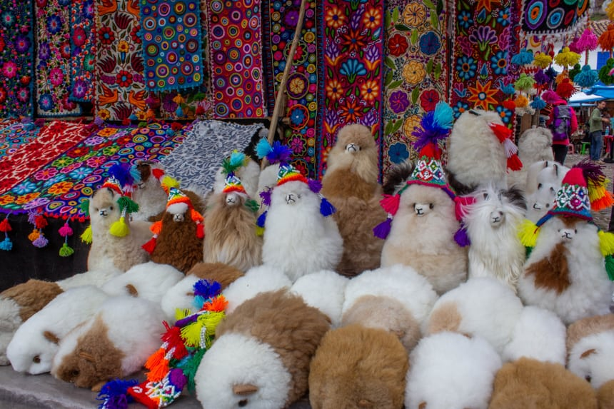 A brightly colored market table filled with plush Llama toys and woven table runners in the Sacred Valley, Peru.