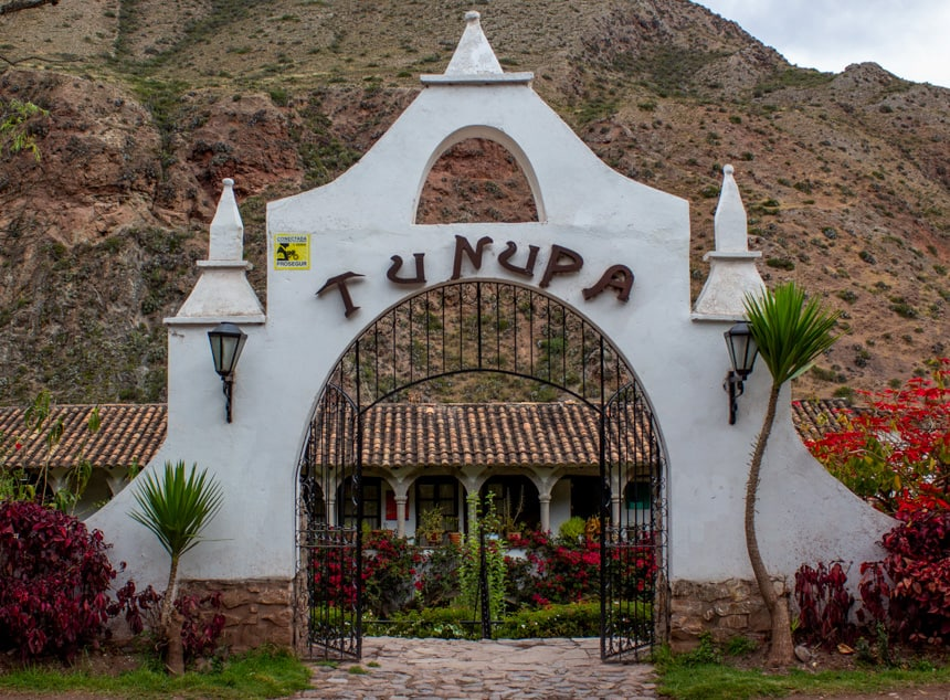 The entry way of Tunupa hotel in the Sacred Valley, Peru. Bright white stone arch with a black gate open to the hotel that sits in front of a dessert like hillside.