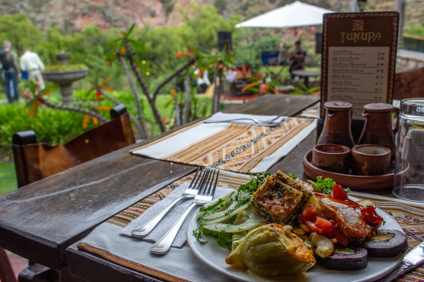 A full plate of varied food set on a table seated outdoors in a lush green garden of a hotel in the Sacred Valley Peru.