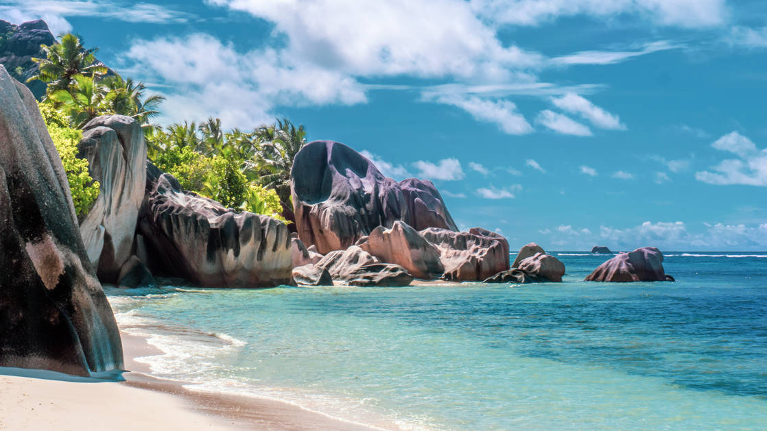 Private beach lined with red boulders & palm trees on a sunny day during the Pearls of the Caribbean luxury cruise.