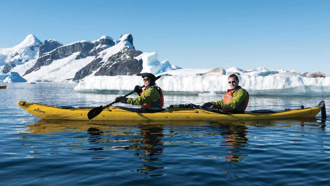 Tandem kayakers in a yellow boat paddle in calm waters with snow-covered mountains in the background, on a sunny day during the Spirit of Antarctica expedition.