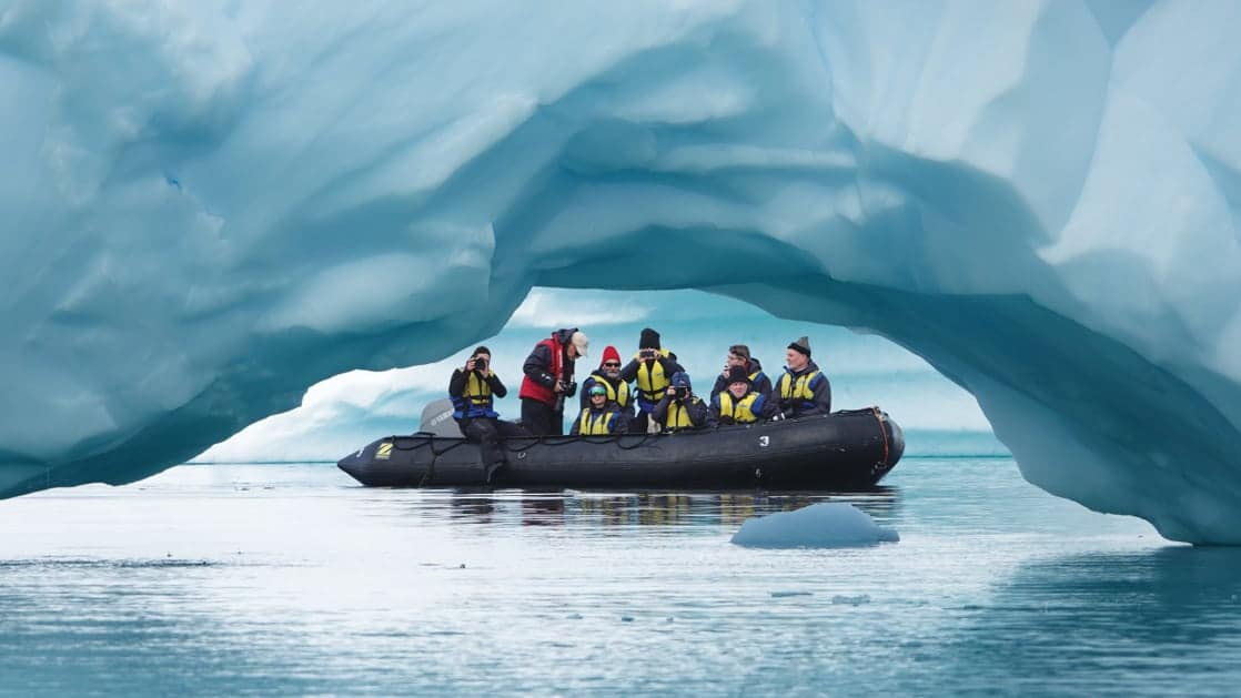 A group of polar travelers in a Zodiac cruises beside an archway in a large blue iceberg during the Spirit of Antarctica expedition.