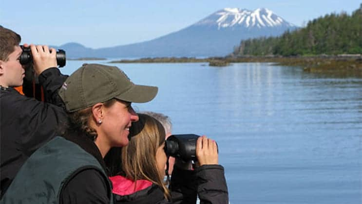 A family looks through binoculars from on deck with green forest & snowcapped mountains in the background, in calm waters during the Kruzof Explorer Custom Alaska Cruise.