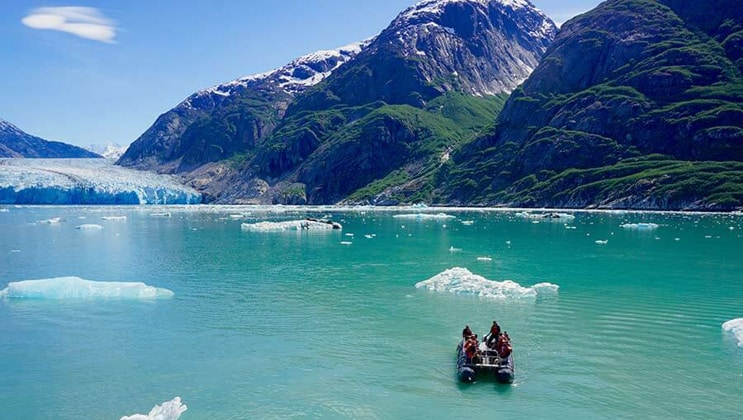 A DIB tender vessel brings Alaska charter guests towards a glacier in turquoise waters on a sunny day during the Kruzof Explorer Custom Alaska Cruise.