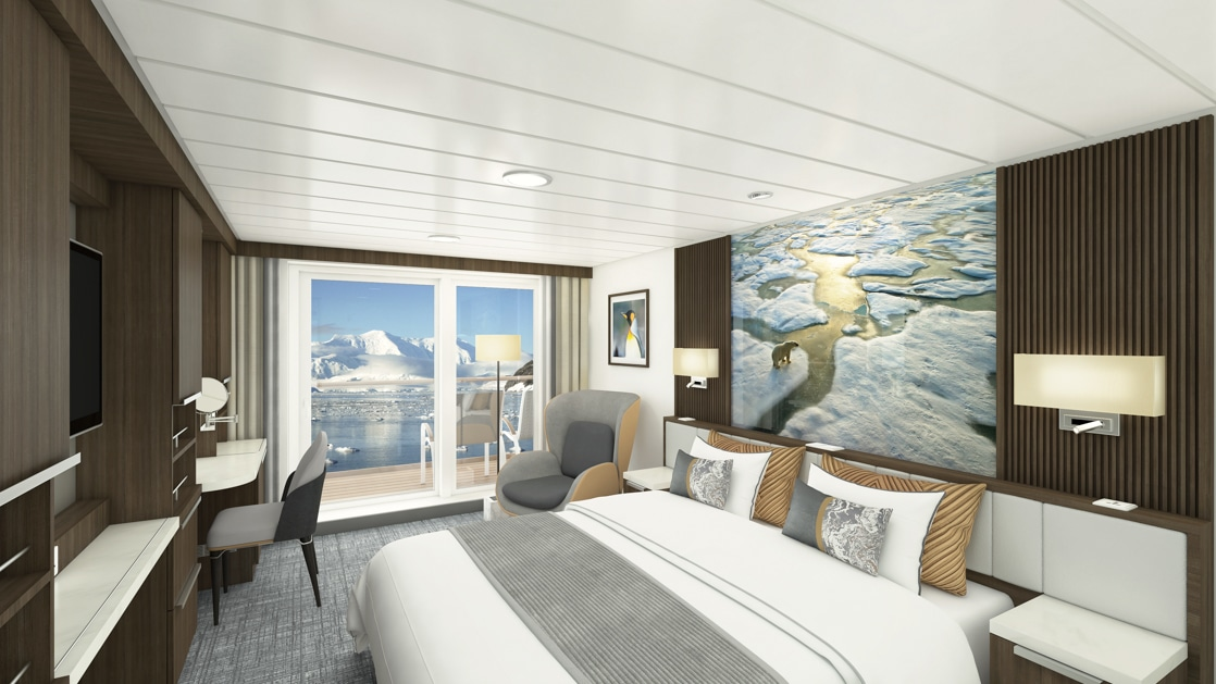Captain's Suite bedroom aboard Sylvia Earle polar ship, with king bed, framed photograph of a polar bear on Arctic ice next to a framed penguin photo, reading lights above headboard, tv, desk, lounge chair & sliding glass door to private balcony.