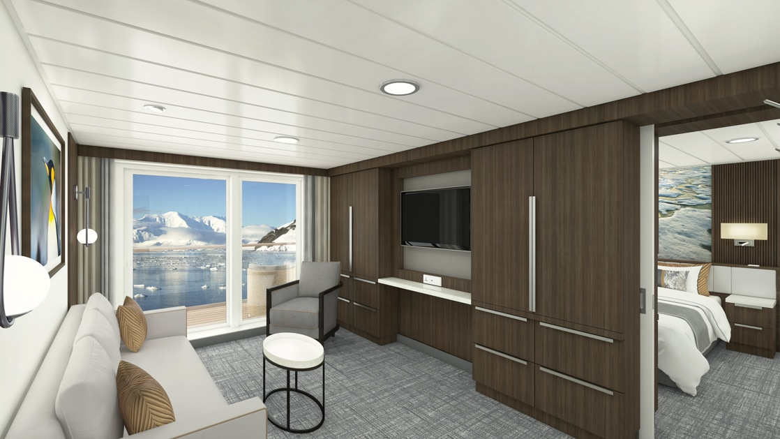 Separate Living room in the Captain's Suite aboard Sylvia Earle polar expedition ship with flatscreen tv surrounded by storage space across from a couch, table, and lounge chair with framed penguin photograph and large sliding glass doors opening to private balcony.