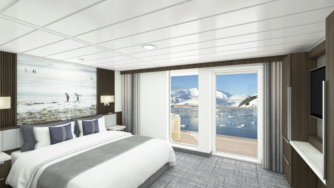 Category A Balcony Stateroom aboard Sylvia Earle polar ship, with white-duvet-covered king bed, large framed penguin photograph, marble bedside tables, flatscreen tv, & sliding glass doors onto private balcony.