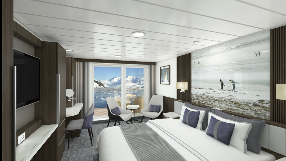 Category B Balcony Stateroom aboard Sylvia Earle polar ship, with white-duvet-covered king bed, large framed penguin photograph, marble bedside tables, flat screen tv, desk, lounge chairs with table, & sliding glass doors onto private balcony.