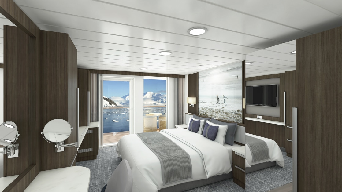 Category C Balcony Stateroom aboard Sylvia Earle polar ship, with white-duvet-covered king bed, large framed penguin photograph, marble bedside tables, flat screen tv, desk, mirrors and wardrobe & sliding glass doors onto private balcony.