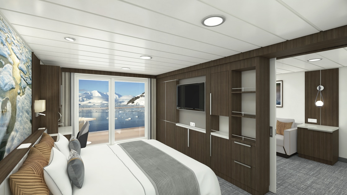 Junior Suite aboard Sylvia Earle polar ship, with white-duvet king bed, flat screen tv surrounded by wardrobe and storage shelves, chair at desk, framed polar landscape photo with reading lights above headboard and entryway to separate lounge room.