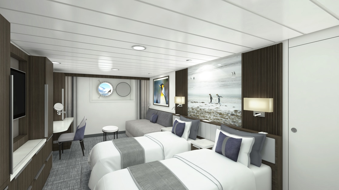 Twin Stateroom aboard Sylvia Earle polar ship, with 2 white-duvet-covered twin beds, marble bedside tables, chair at desk, wardrobe, flatscreen tv & sofa next to porthole.