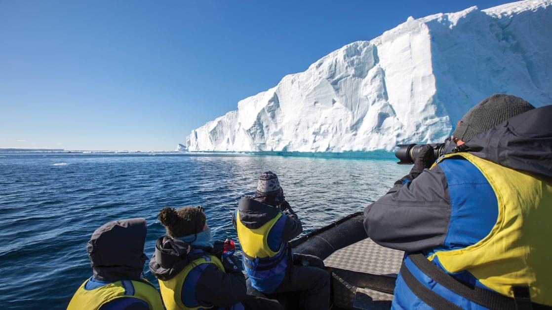 A group of polar travelers in yellow life jackets sit in a Zodiac and photograph a large tabular iceberg on a sunny day during the Active & Wild Antarctica Air Cruise.