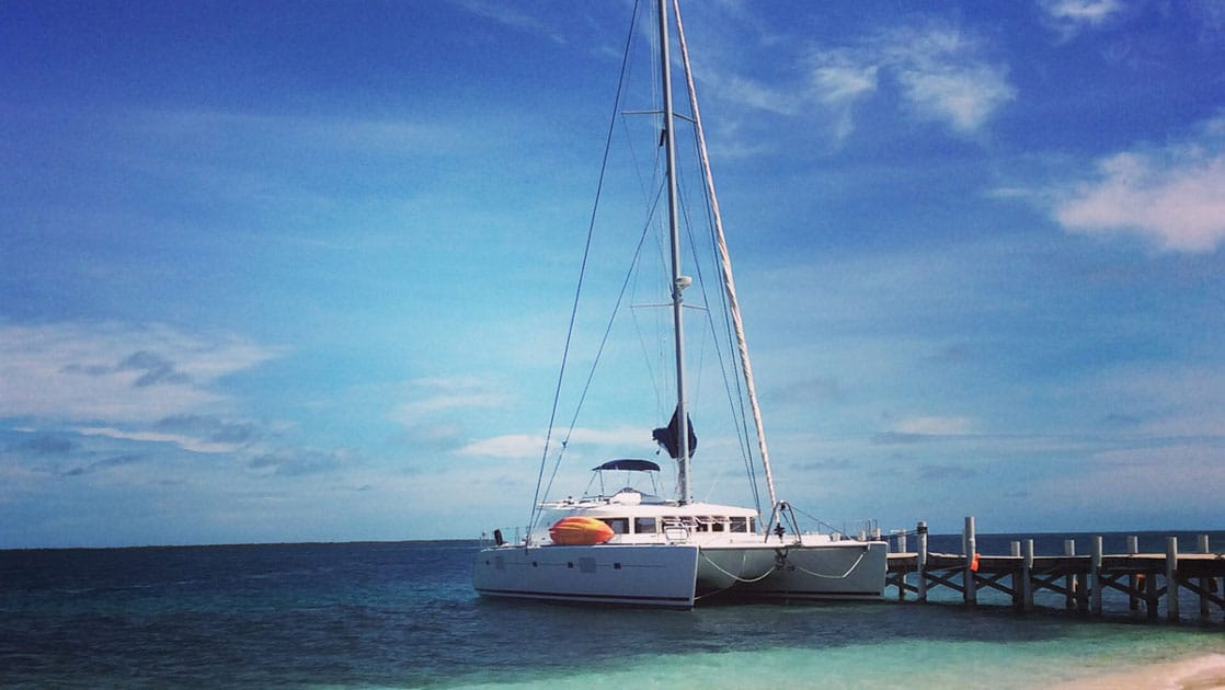 White catamaran Sand Star sits docked in turquoise water by a white-sand beach on a sunny day in Belize.